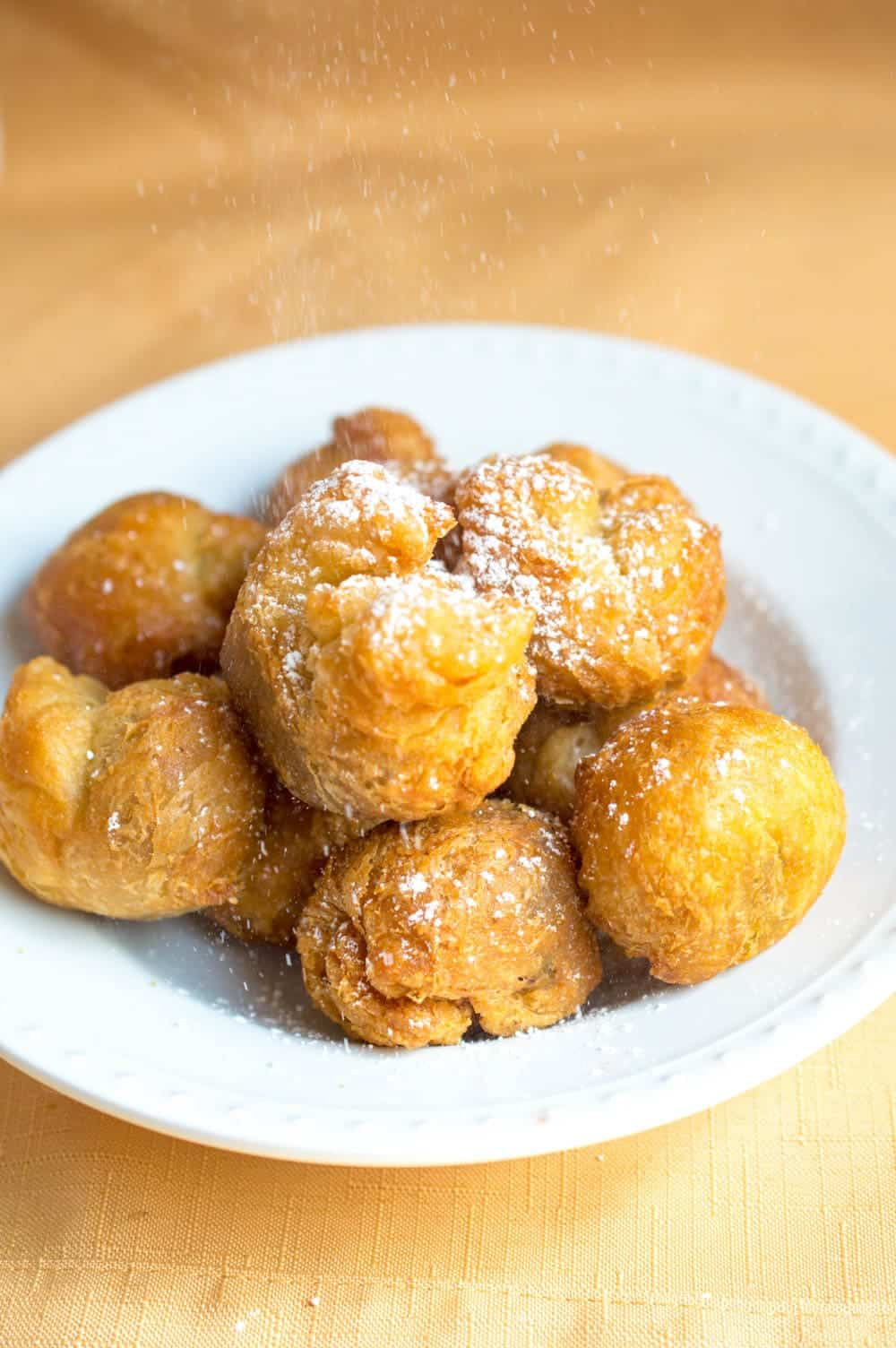 fried nutella dumplings on a plate with powdered sugar on top
