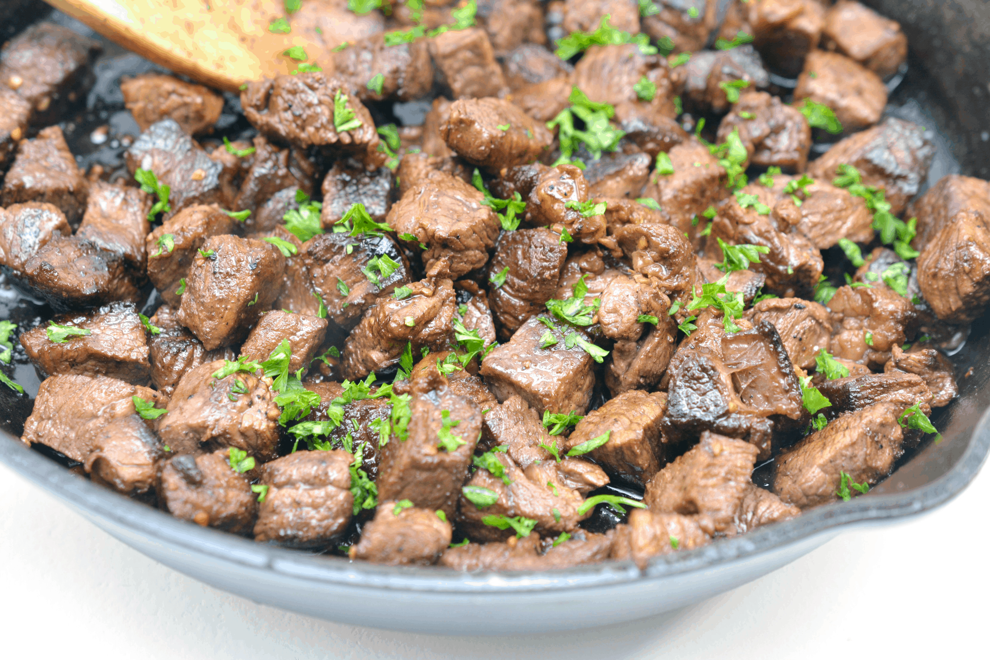 garlic steak bites in a pan topped with fresh herbs