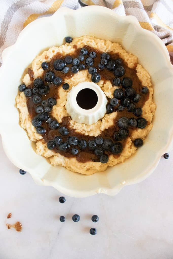 white bundt pan with coffee cake batter and blueberries