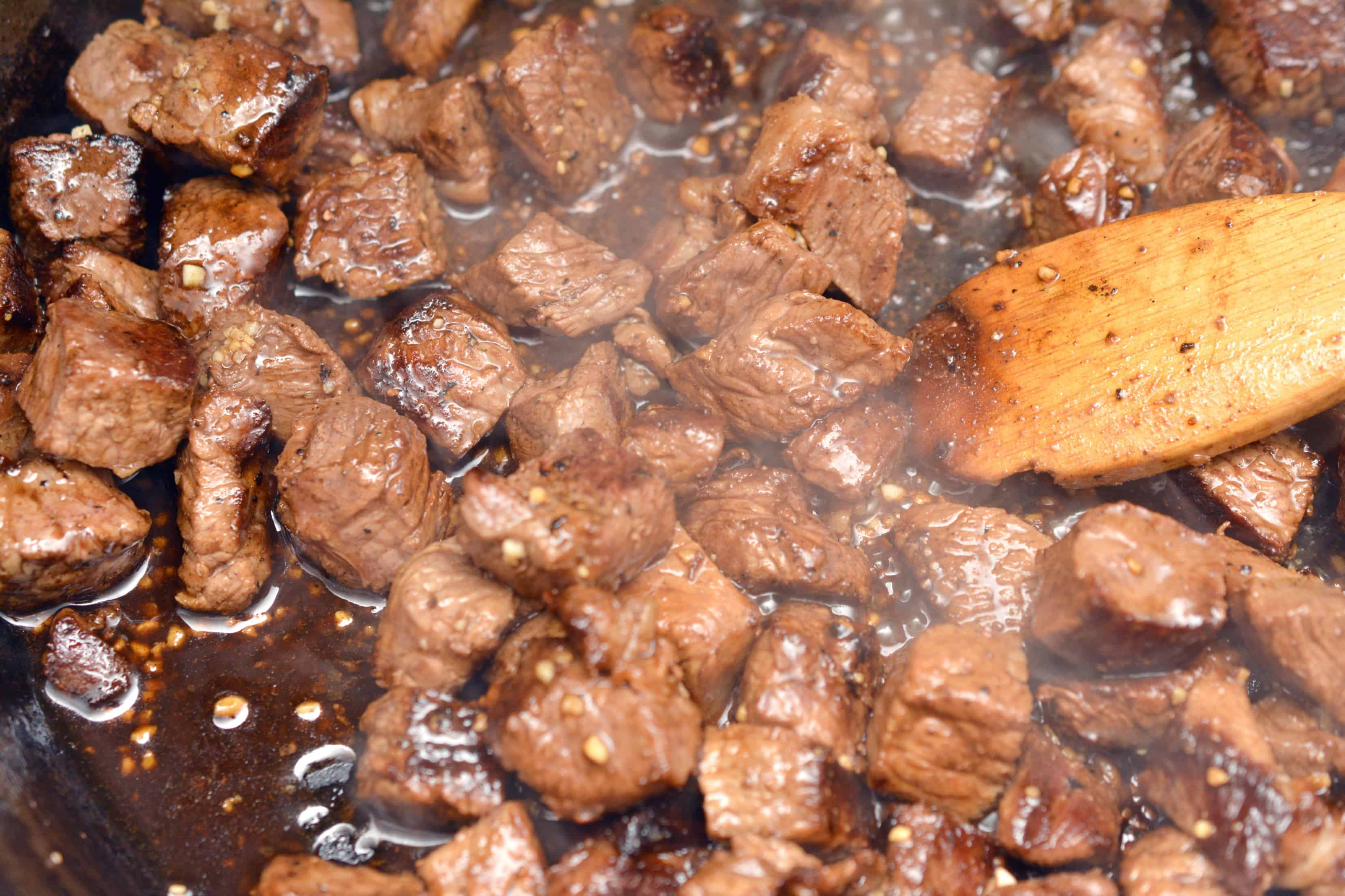 steak bites simmering in pan on stove