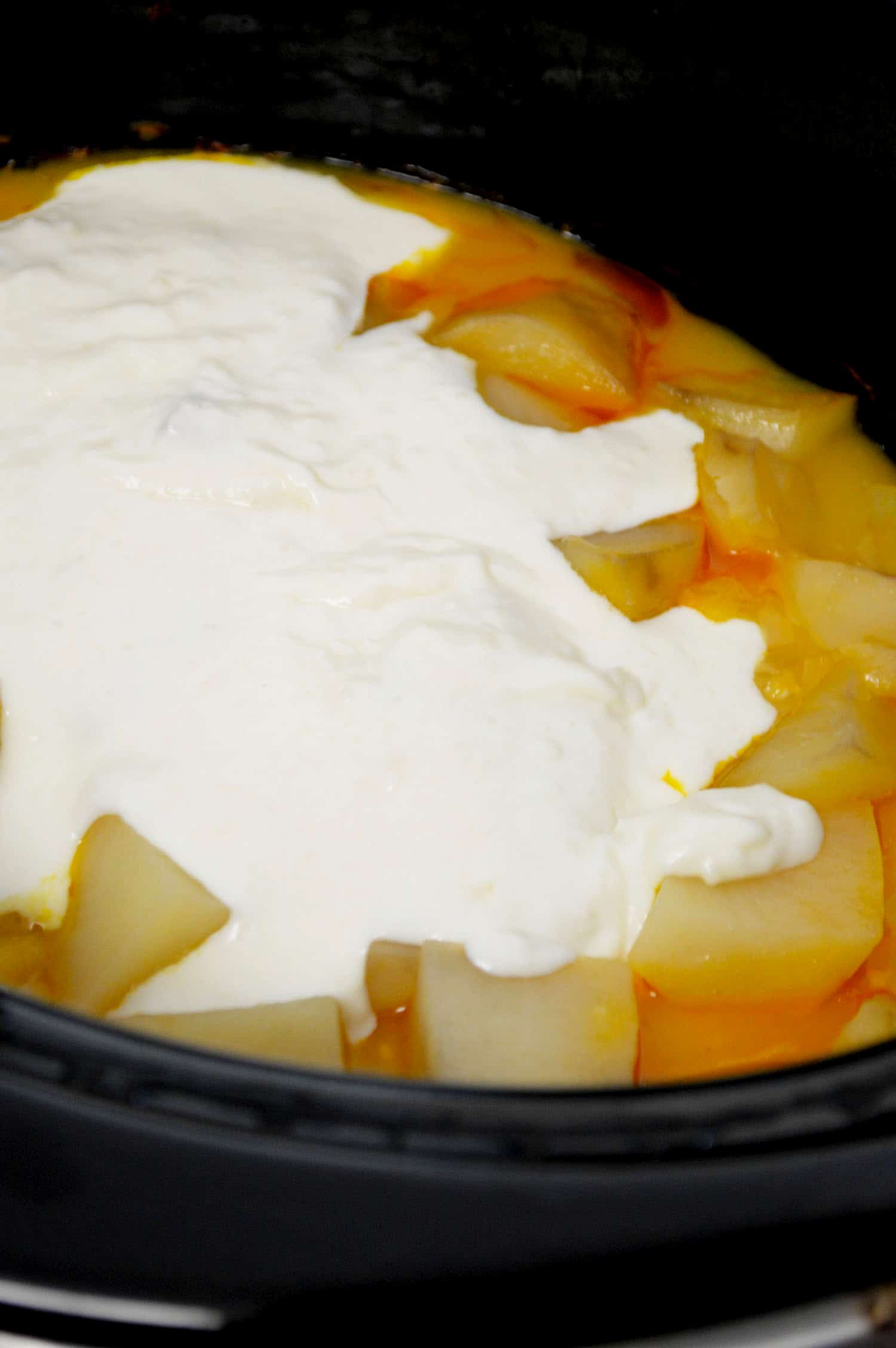 mixing slow cooker potato soup