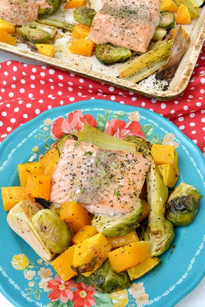 lemon pepper salmon on a plate with sheet pan behind it