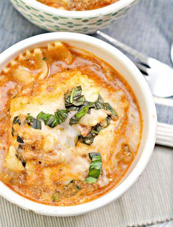 A small bowl of prepared instant pot lasagna on a blue cloth