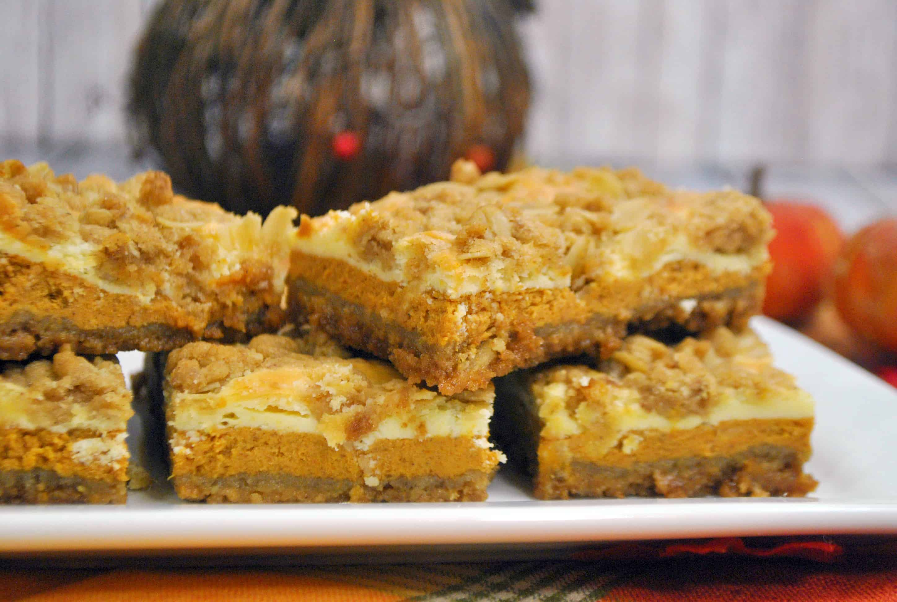 pumpkin cheesecake bars stacked up and on table