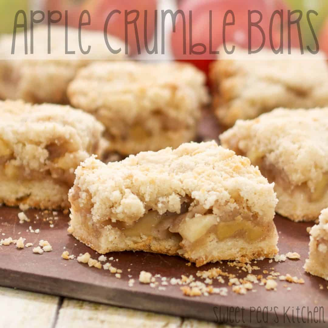 Apple crumble bars on a wooden board with one bite out of the one in front