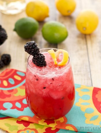 A small glass of blackberry bramble sitting on a colorful napkin on a wooden surface
