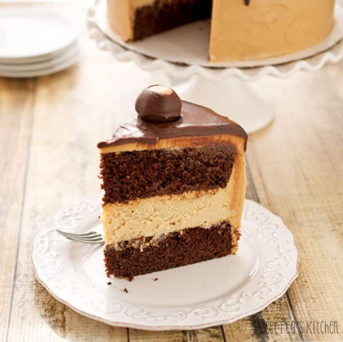 Buckeye Peanut Butter Cheesecake Layer Cake one slice sitting on a white saucer that is on a wooden surface