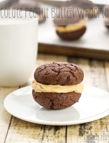 A single whoopie pie sitting on a saucer with a cup of milk behind it