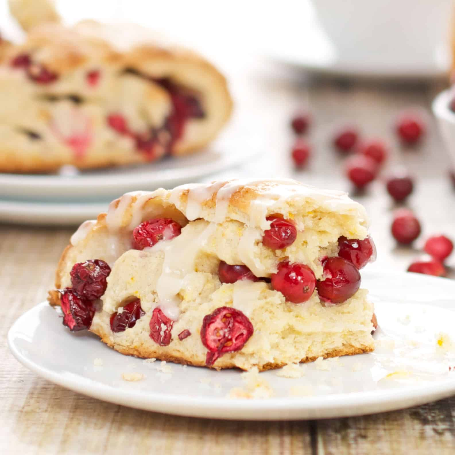plate with cranberry scone and fresh cranberries