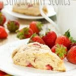 Up close picture of a baked fresh strawberry scone sitting on a white saucer with colorful napkin back
