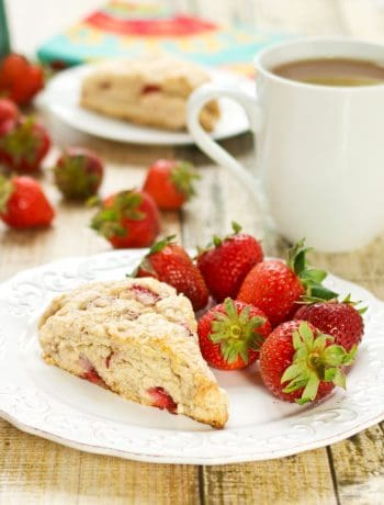 fresh strawberry scones recipe with a piece sitting on a white plate with fresh strawberries and coffee in the background