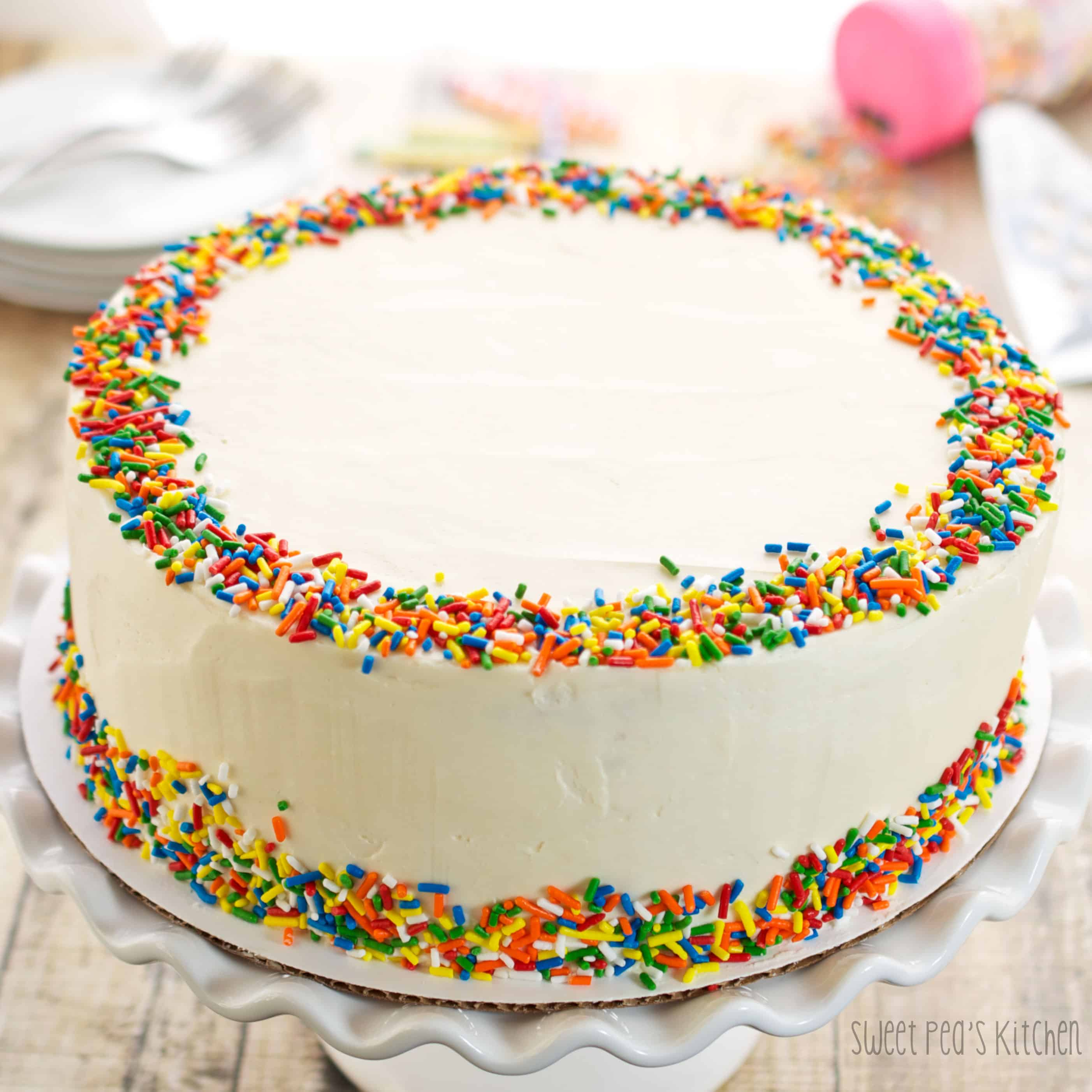 funfetti cake with sprinkles on a white cake stand