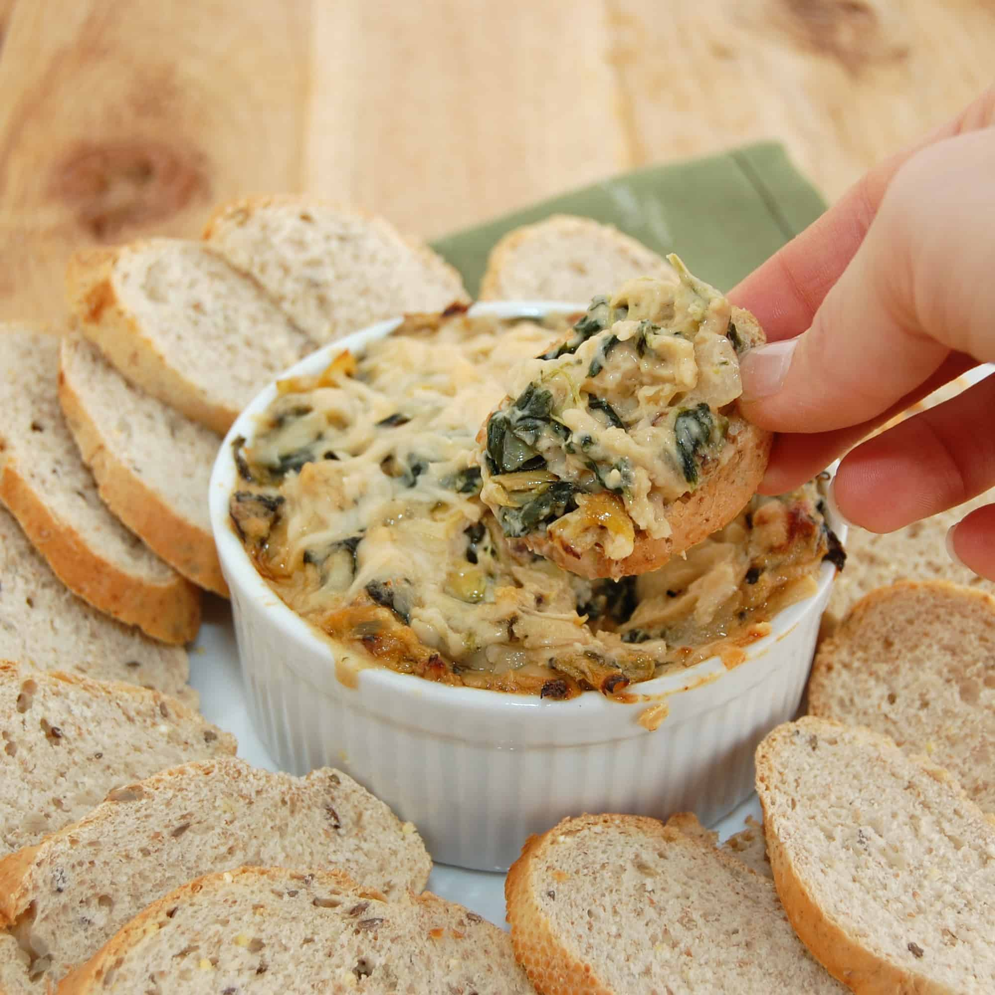 dipping bread into spinach dip