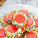 Plate with multiple cooked iced thumbprint cookies with sprinkles