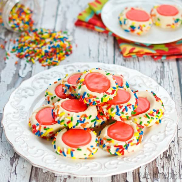 A plate of icing filled thumbprint cookie recipe with red icing and sprinkles
