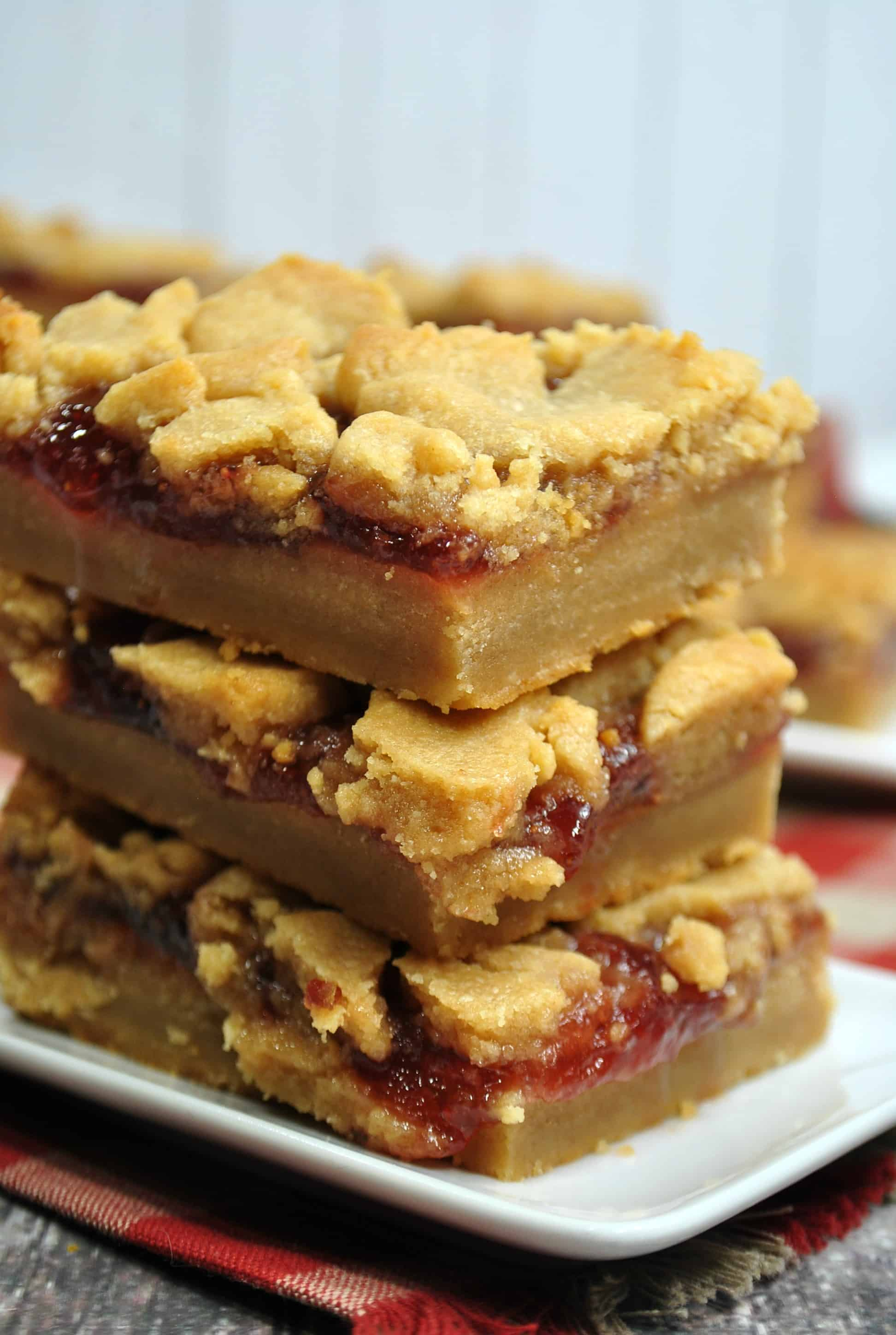 stack of peanut butter and jelly bars on a white plate
