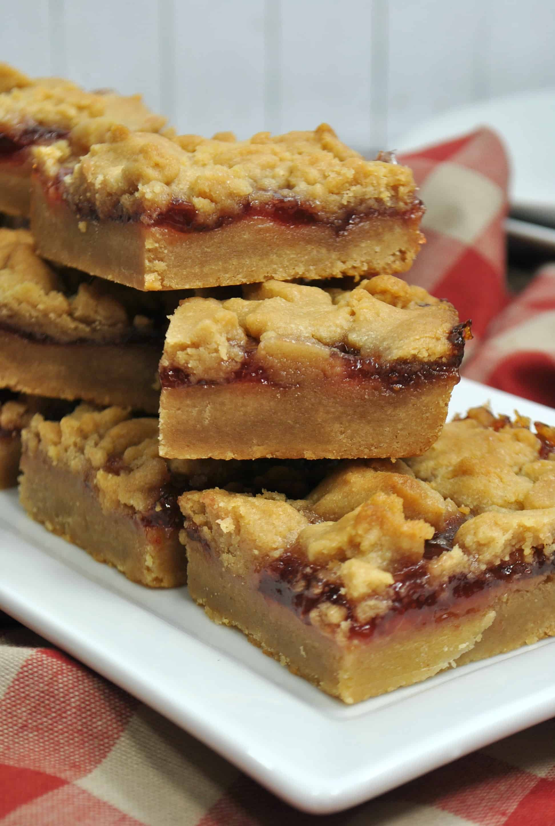 peanut butter and jelly bars in a stack on a white plate