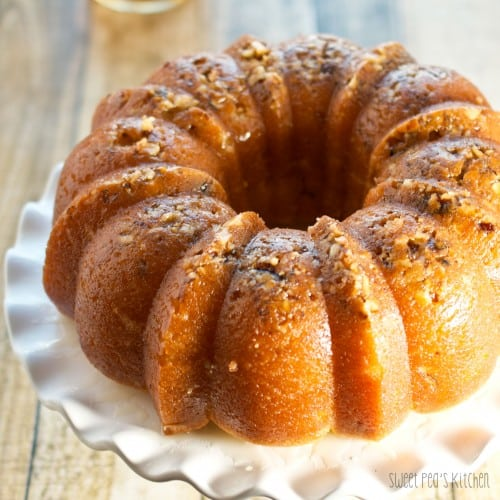 whole rum cake on a white cake stand