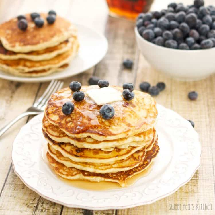 blueberry pancakes on a plate with blueberries
