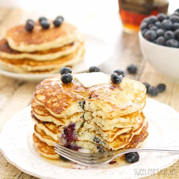 blueberry pancakes with butter on a white plate