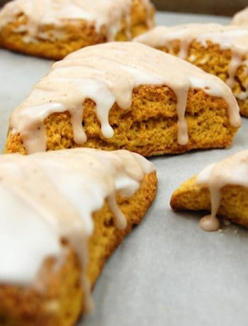 Pumpkin Scones prepared sitting on parchment paper topped with glaze