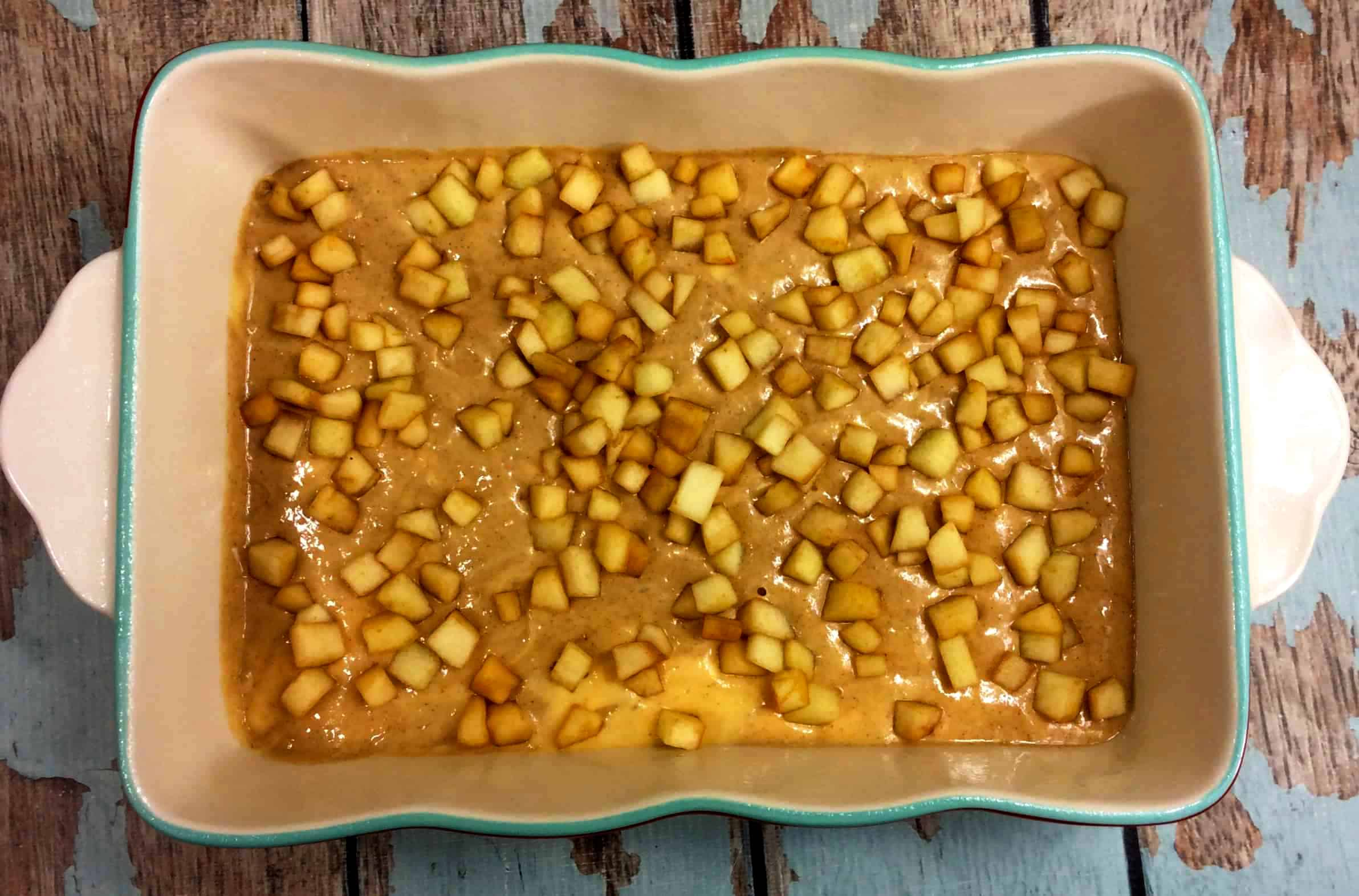 cake batter and apples in a baking dish