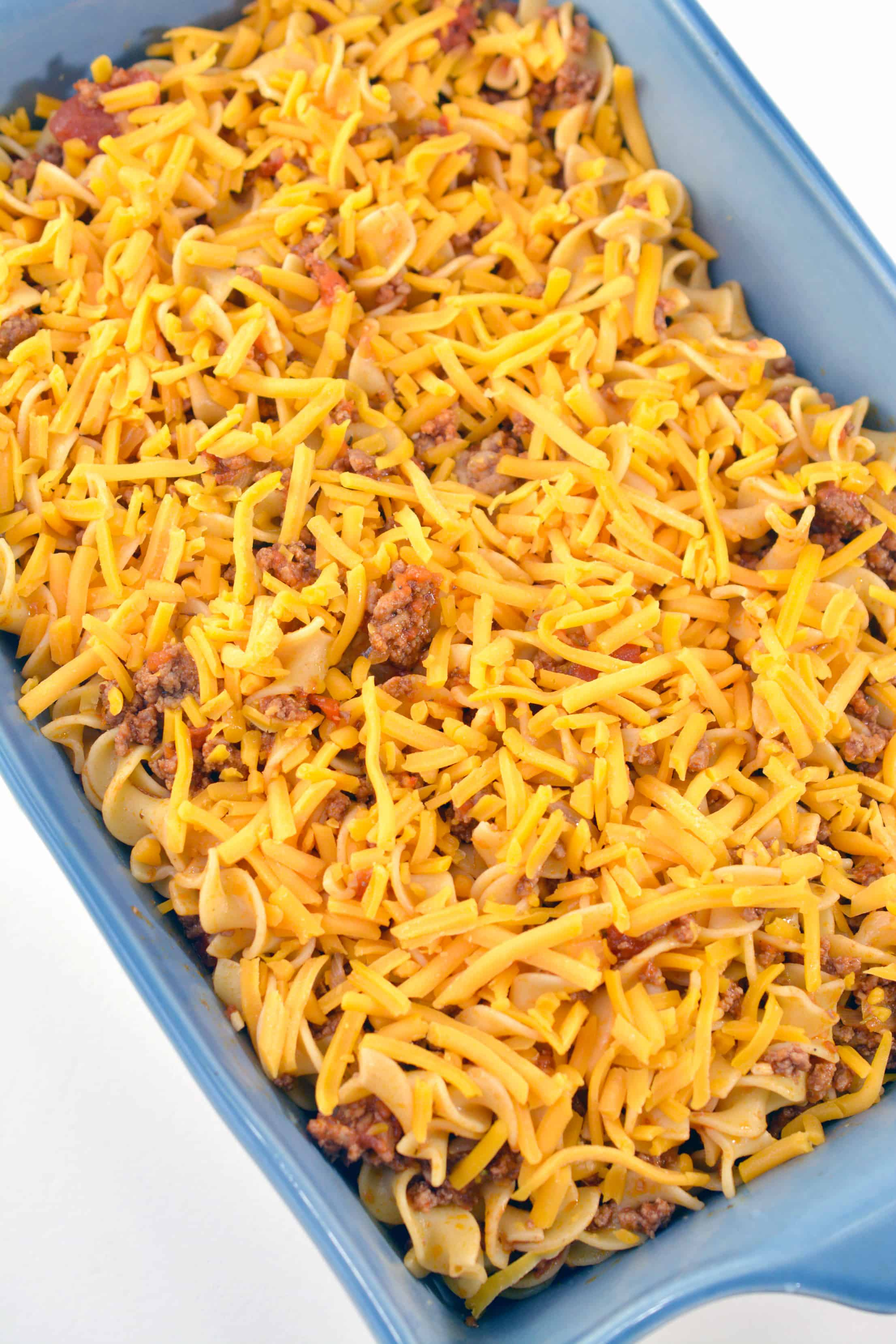 cheese over noodles and beef in casserole dish