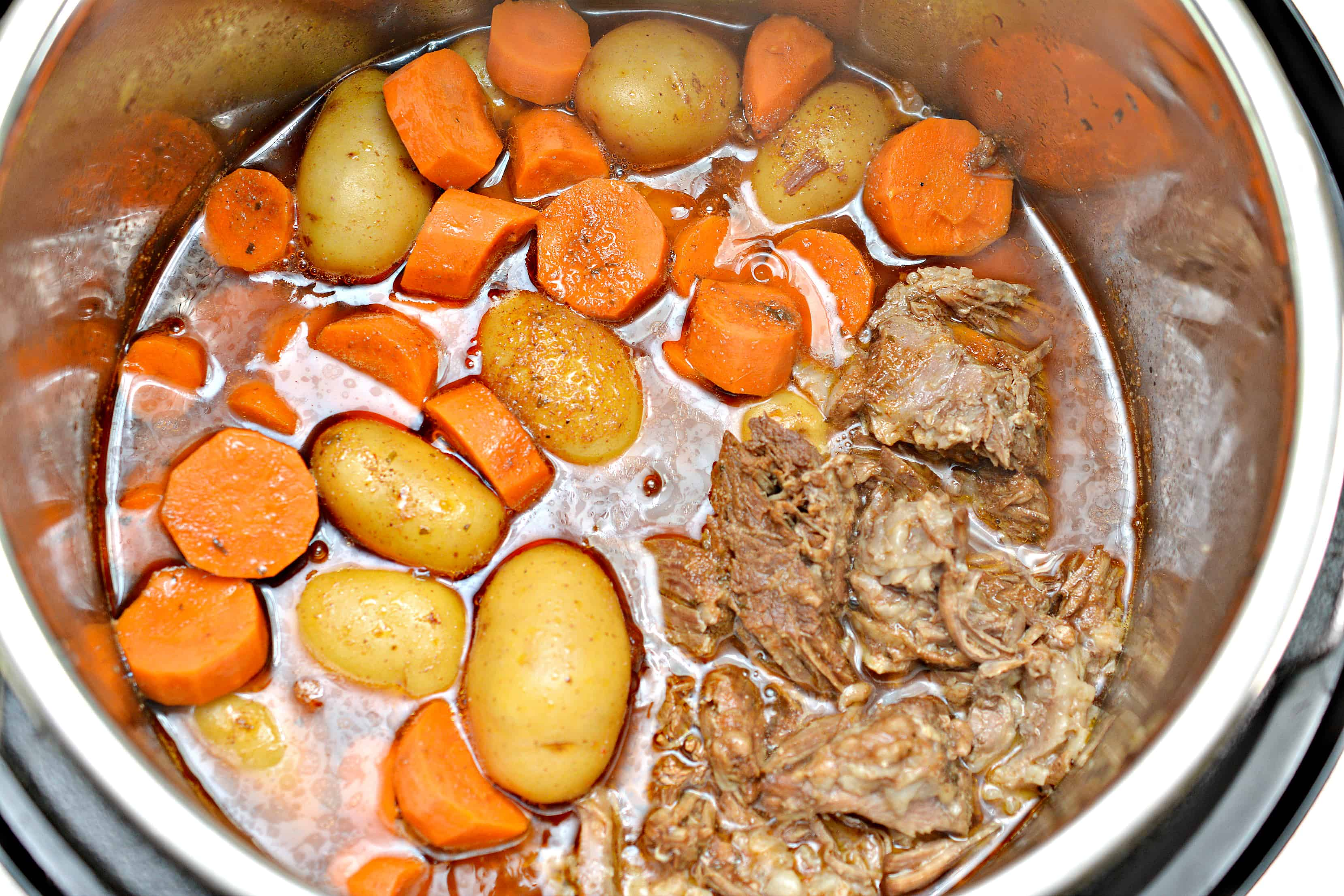 beef and potatoes with carrots in the pot