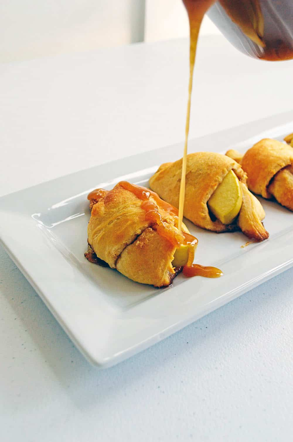 caramel being drizzled over apple crescent rolls