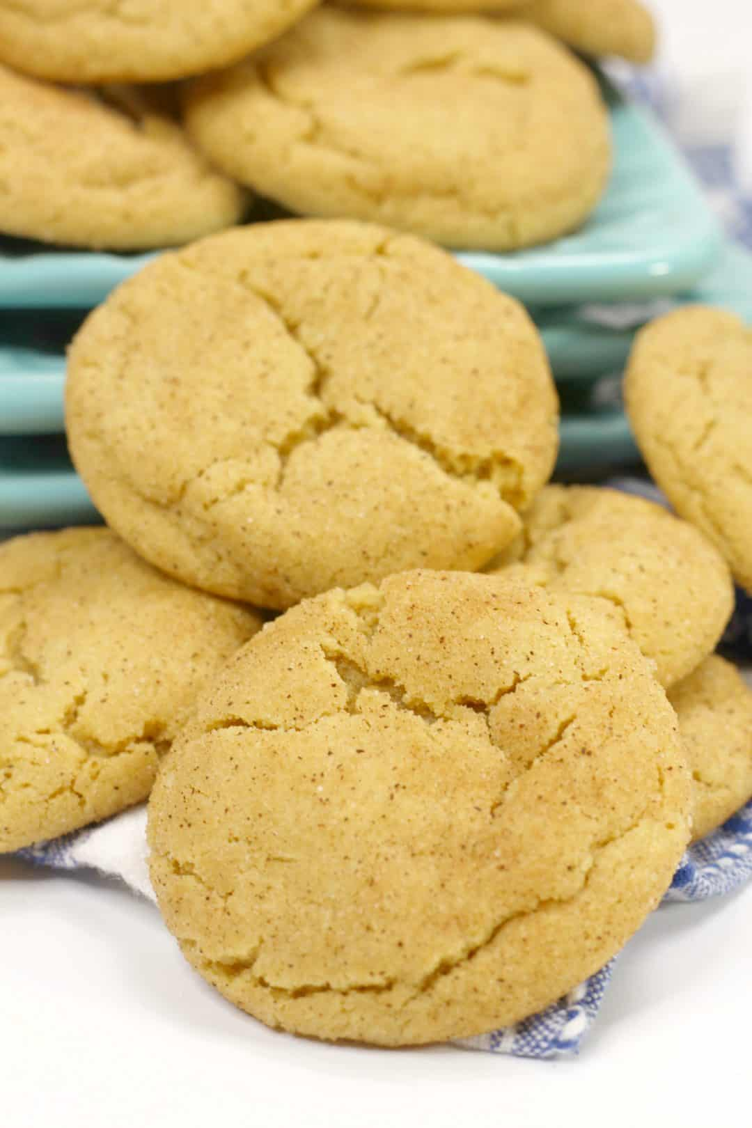 Stacks of Easy snickerdoodle cookies laying on a white surface next to teal plates