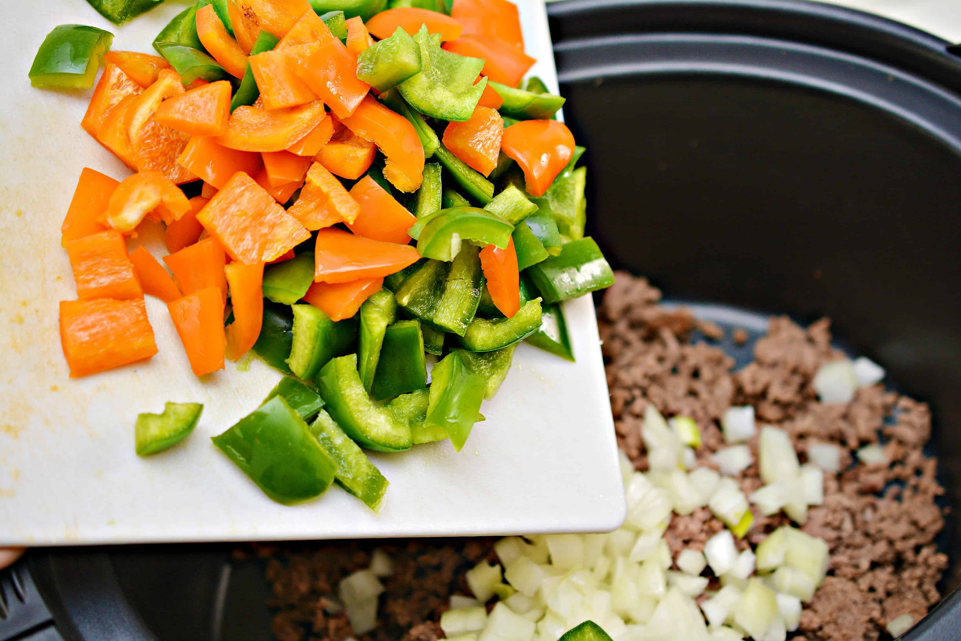 green and orange diced peppers being added to soup