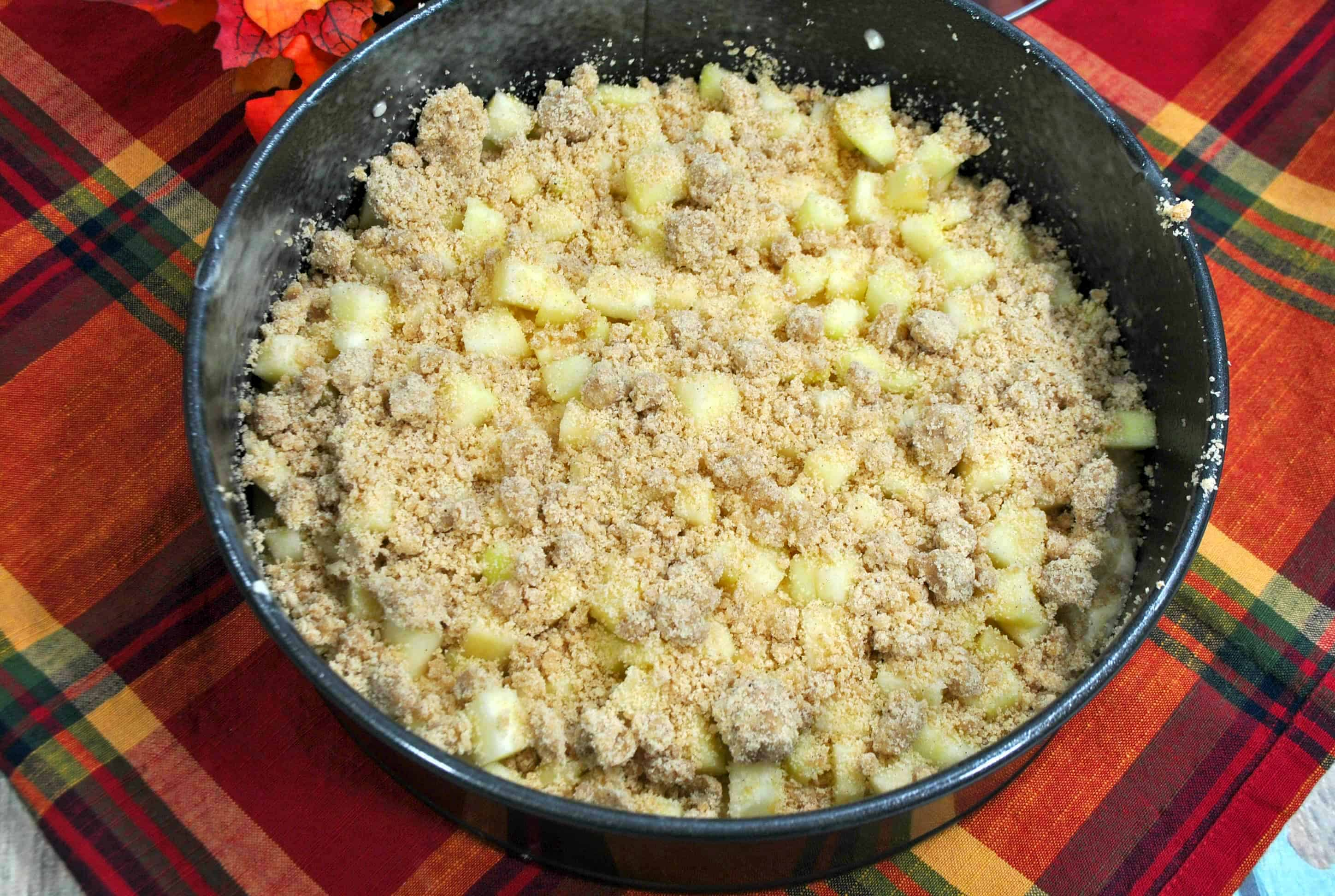 apple crumb filling on top of cake batter in a springform pan