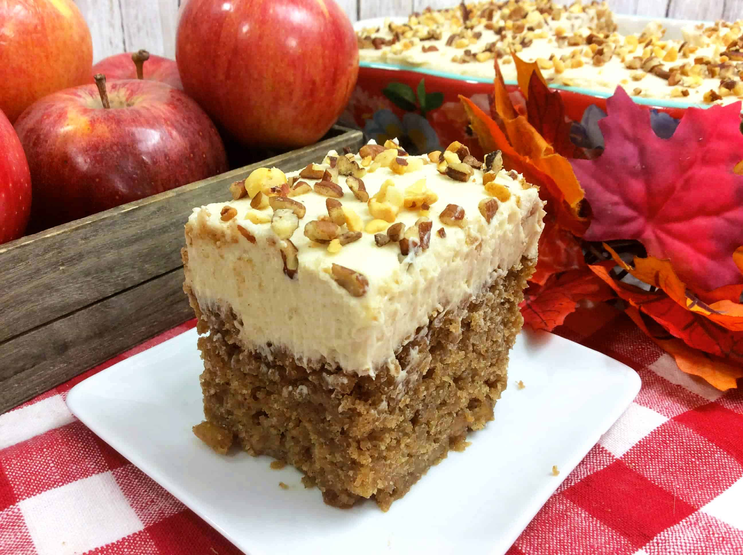 Orange Apple Spice Cake on a white plate with apples and a red checked table cloth