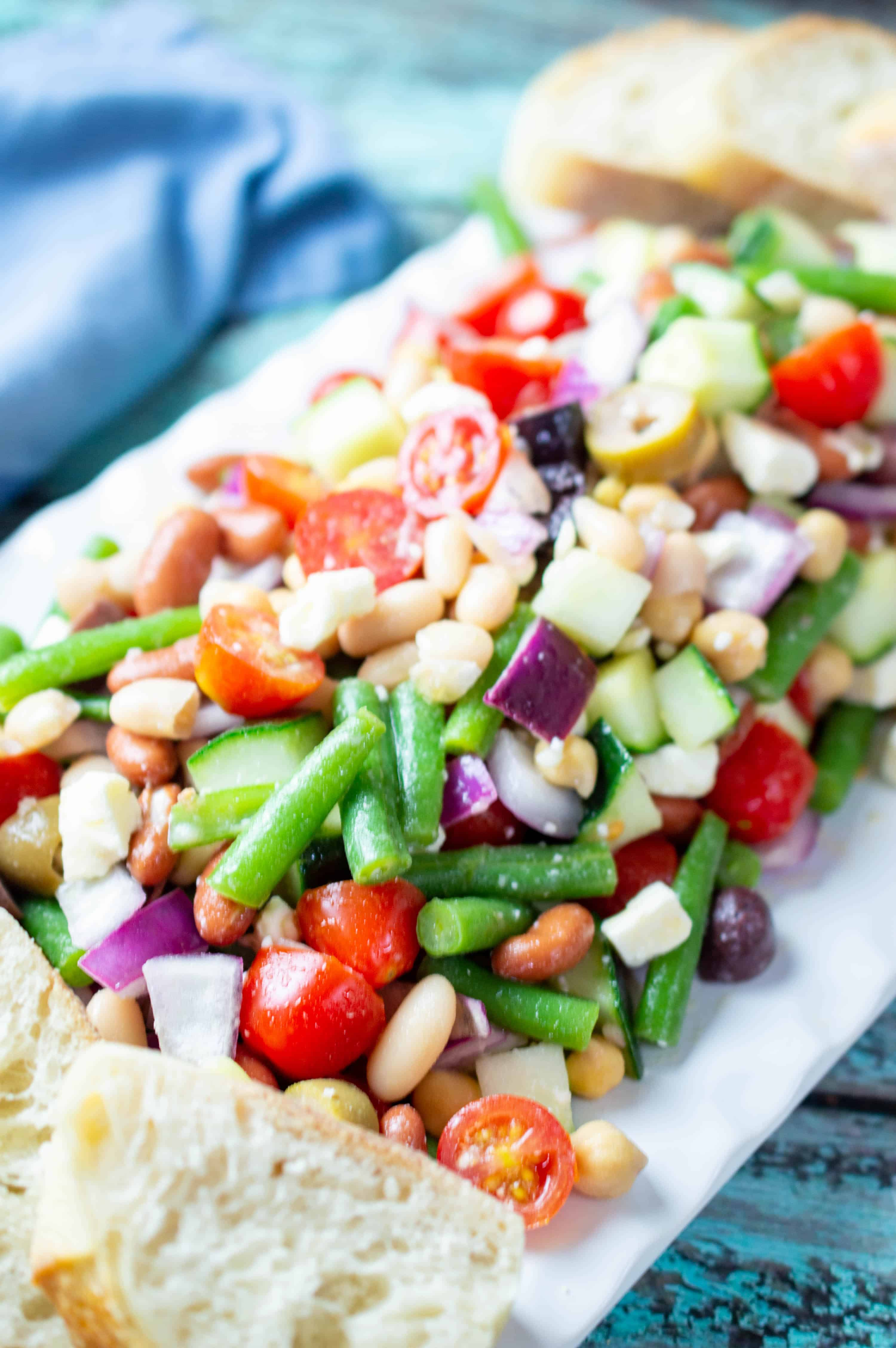Greek bean salad on a white plate with blue next to it