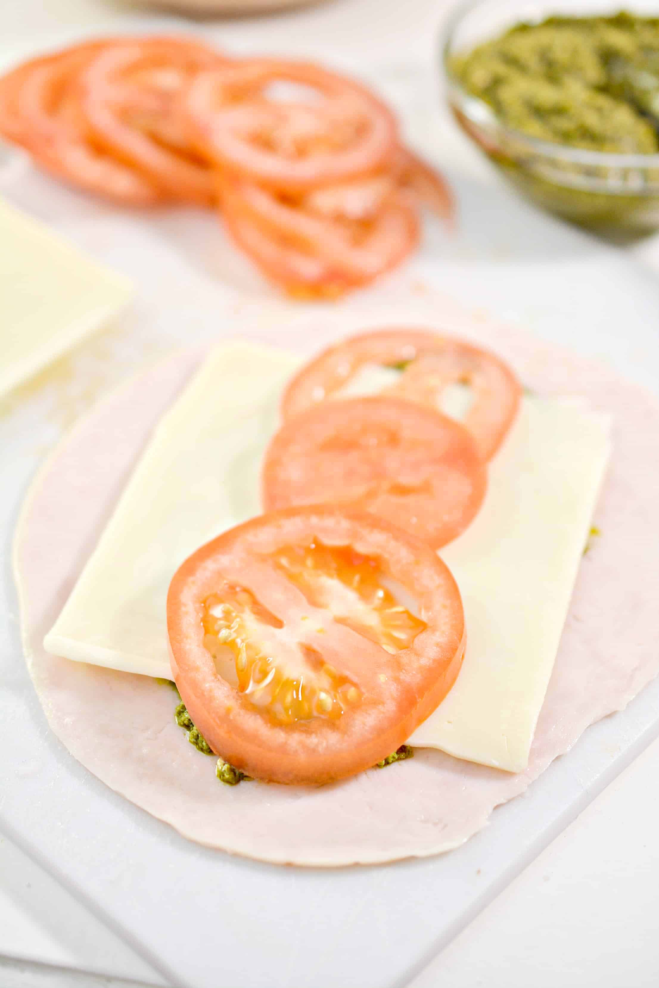 tomatoes on cheese, pesto and turkey