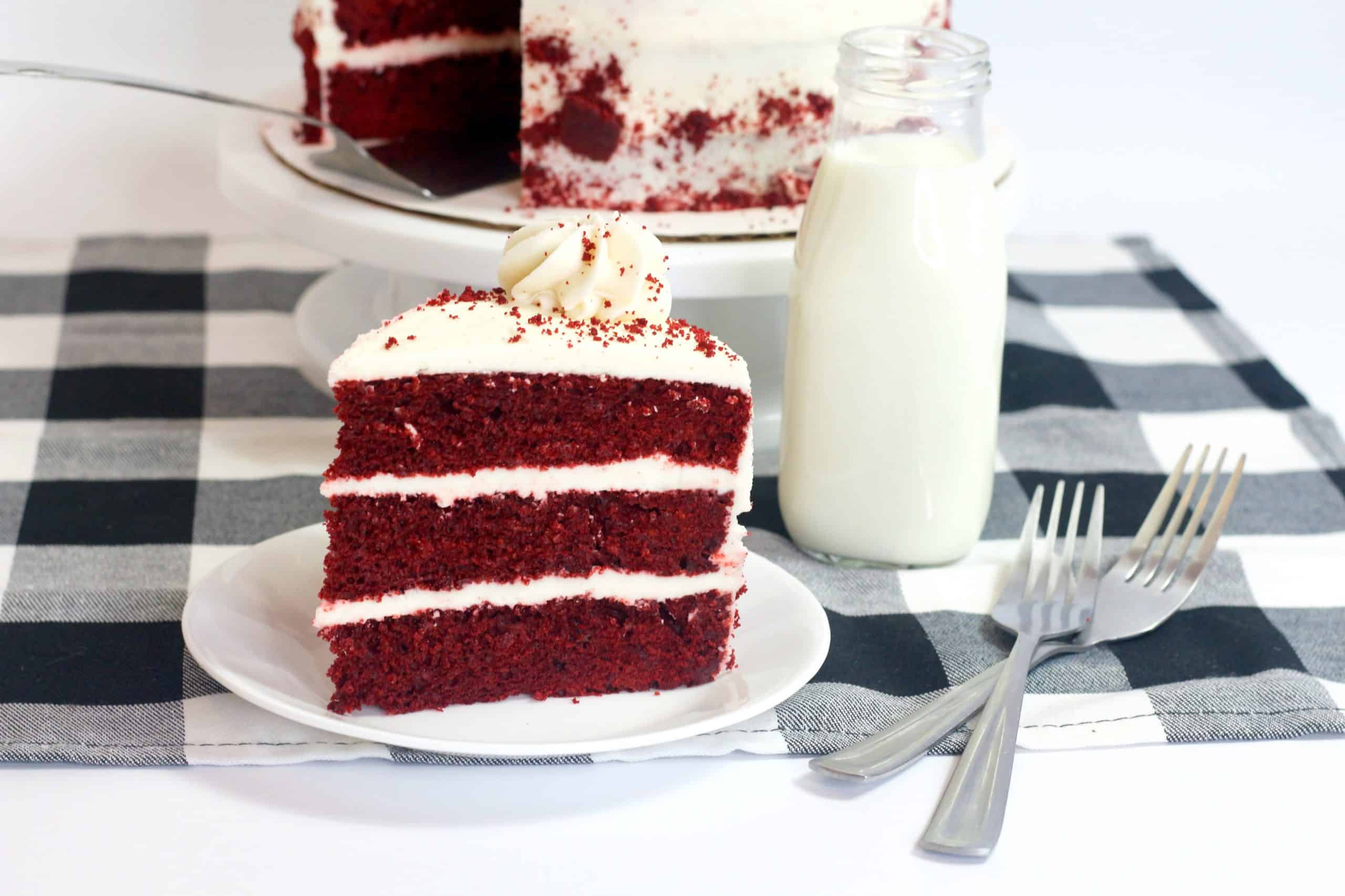slice on red velvet cake on a white plate with a checkered napkin and milk