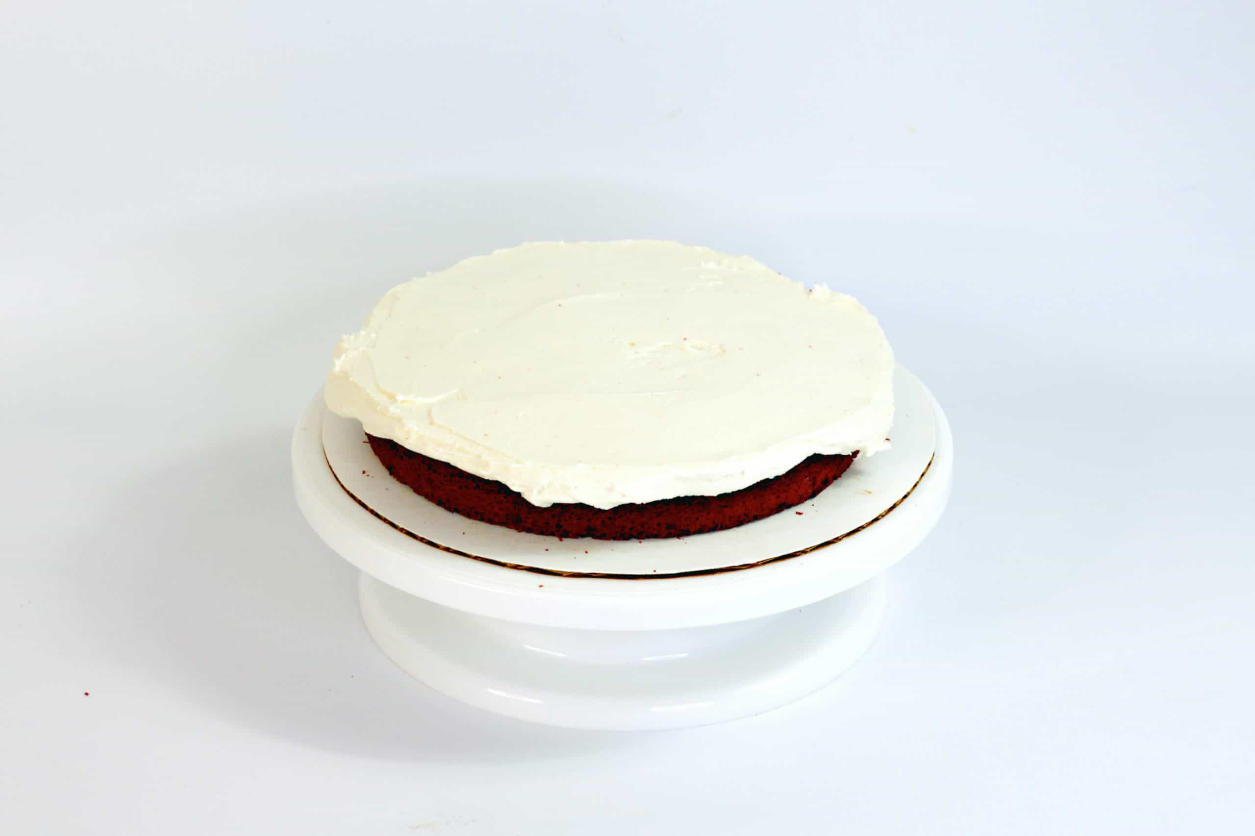 cream cheese frosting on top of red velvet layer